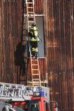 有氧气罐火的勇敢的消防队员在举行的锻炼期间 库存图片