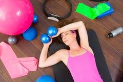 有氧运动妇女疲倦的休息的位于在席子 免版税库存图片