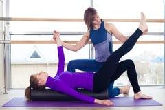 有氧运动普拉提个人教练员帮助的妇女 免版税库存照片