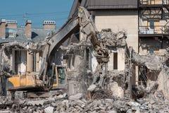有水力剪的挖掘机折除的房子,爆破的废墟 库存图片