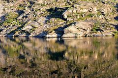 有水反射的皮船的河和人 岩石、植被和颜色,日落光 Ezaro,加利西亚,西班牙 免版税库存图片
