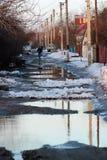 有水坑的农村路和解冻的雪春天 免版税库存照片