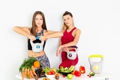 有水壶响铃的美丽的年轻女人和在白色背景的健康菜 概念饮食 - 图象 免版税库存图片