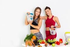 有水壶响铃的美丽的年轻女人和在白色背景的健康菜 概念饮食 - 图象 库存图片
