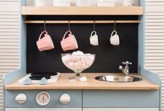 有水槽的婴孩减速火箭的厨房和火炉,在脉管的桃红色marshmellows 库存图片