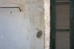 有水泥和权利木绿色快门,一个老大厦的墙壁的抽象背景内部斑点的白色肮脏的墙壁  库存图片