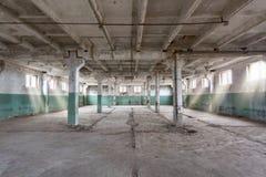 有水泥墙壁、地板、窗口和柱子的工业仓库在建筑,改造,整修前 免版税图库摄影