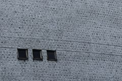 有水泥纹理和三个黑角规窗口的灰色墙壁 免版税库存图片