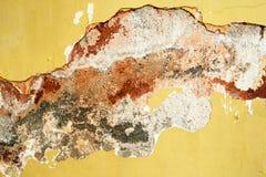 有水泥背景镇压的老黄色被绘的墙壁与红色,灰色和白色污点的 免版税库存图片