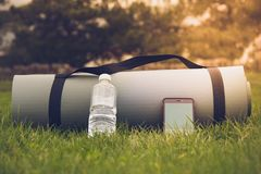 有水瓶和电话的瑜伽席子在柔光的绿草 库存图片