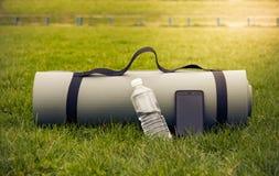 有水瓶和电话的瑜伽席子在柔光的绿草 免版税库存图片