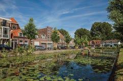 有水生植物、街道在银行和砖房子的沿途有树的运河在一个晴天在韦斯普 免版税库存图片
