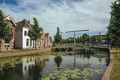 有水生植物、街道在银行,砖房子和开启桥的沿途有树的运河在一个晴天在韦斯普 库存图片