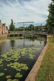 有水生植物、街道在银行,砖房子和开启桥的沿途有树的运河在一个晴天在韦斯普 免版税库存图片