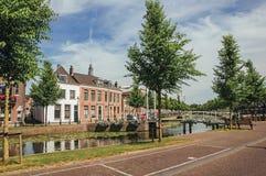 有水生植物、街道在银行,砖房子和开启桥的沿途有树的运河在一个晴天在韦斯普 库存照片