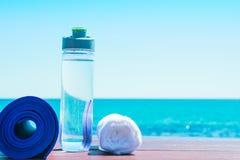 有水白色毛巾的滚动的瑜伽席子瓶在与绿松石海蓝天的海滩在背景中 阳光 r 免版税图库摄影