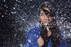 有水飞溅的活跃妇女雨衣在点燃bl的演播室 免版税库存照片