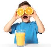 有汁液和橙色一半玻璃的逗人喜爱的小男孩  图库摄影