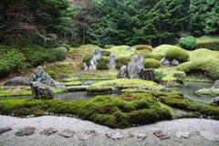 有池塘、岩石、石渣和青苔的平安的日本禅宗庭院 免版税图库摄影