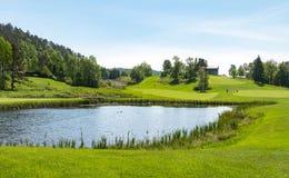 有池塘、蓝天和绿色自然的高尔夫球场 免版税库存照片