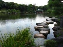 有池塘和垫脚石的传统日本庭院 免版税库存图片