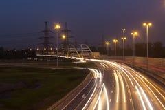 有汽车光足迹的高速公路 库存图片