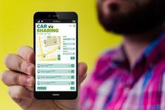有汽车分享的app行家智能手机在屏幕上 免版税库存照片