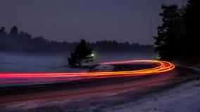 有汽车尾巴光的斯诺伊有雾的森林公路 免版税图库摄影