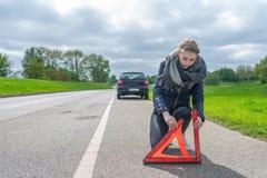 有汽车故障的一名妇女在街道上把警告三角放 免版税库存图片