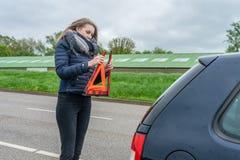 有汽车故障的妇女在她的汽车后登上了警告三角 库存图片