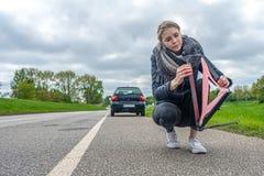 有汽车故障的妇女建立她的警告三角 免版税库存照片