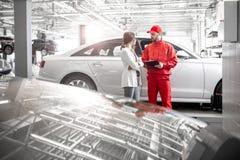有汽车机械师的妇女客户汽车服务的 库存照片