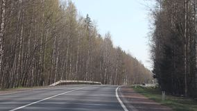 有汽车的俄国柏油路 沿路的树 汽车在路去 俄罗斯,列宁格勒地区2019年4月30日 股票视频