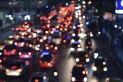 有汽车的被弄脏的五颜六色的夜光城市,抽象backgroun 免版税库存图片