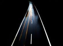 有汽车的路单独在与模糊的光的晚上 库存图片