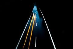 有汽车的路单独在与模糊的光的晚上 免版税库存照片