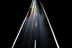 有汽车的路单独在与模糊的光的晚上 库存照片