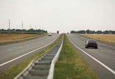有汽车的,秋天沿边的麦田柏油路 免版税库存图片
