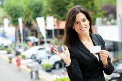 有汽车钥匙的女推销员在商品交易会 库存图片