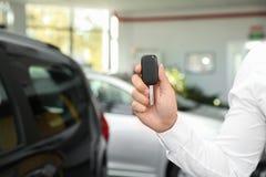 有汽车钥匙的年轻人在经销权中 免版税库存照片