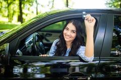 有汽车钥匙的愉快的微笑的少妇 驱动 免版税库存照片