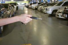 有汽车钥匙的手在停车场 库存照片