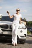 有汽车钥匙的美丽的年轻白肤金发的妇女 免版税图库摄影