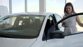 有汽车钥匙的画象女孩,愉快的女性顾客在汽车经销权中把握手中关键到新的汽车,妇女,车 股票录像