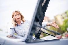 有汽车麻烦的妇女 免版税库存照片