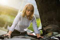 有汽车麻烦的成熟妇女 免版税库存图片