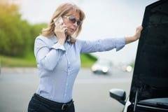 有汽车麻烦的成熟妇女 库存图片