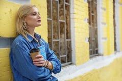 有沉思政券的妇女在街道上的咖啡休息 库存图片