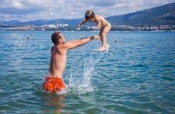 有沐浴在海的年轻儿子的爸爸 免版税图库摄影