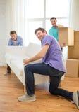 有沙发和箱子的微笑的朋友在新的家 免版税库存图片